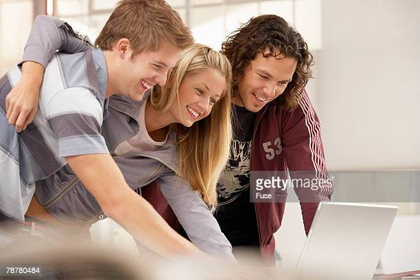 Three Friends Sharing Laptop