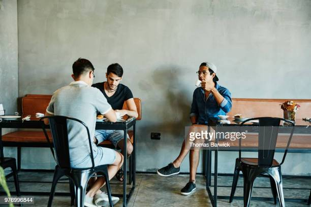 Three friends sharing pastries and coffee at table in bakery