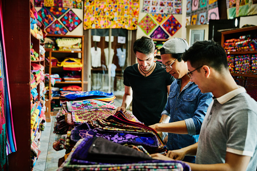 Three friends shopping for hand made goods in local shop while on vacation - gettyimageskorea