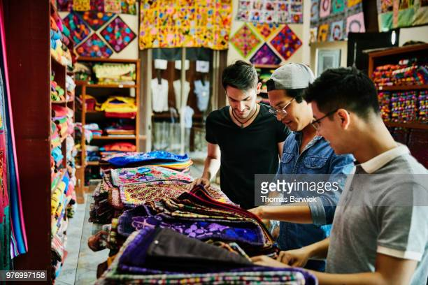 three friends shopping for hand made goods in local shop while on vacation - merida mexico stock photos and pictures