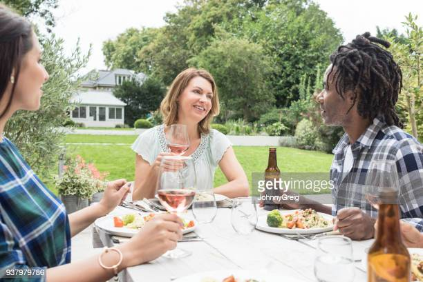 Three friends sitting at table outdoors enjoying dinner