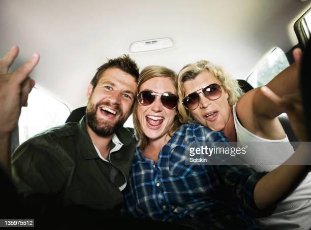 Three friends sitting in car, having fun