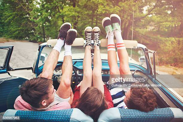 Three friends sitting in convertible with feet up on windscreen