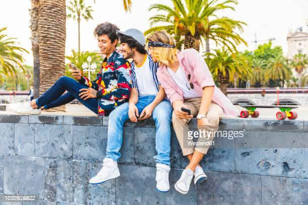 three friends sitting on a wall looking at cell phone - men fashion stock pictures, royalty-free photos & images