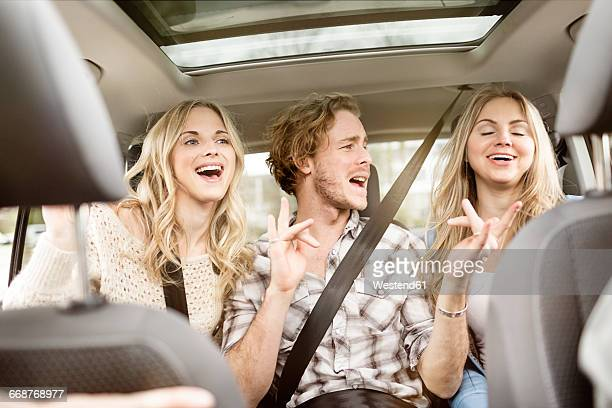 three friends sitting on backseat of car singing together - cantare foto e immagini stock