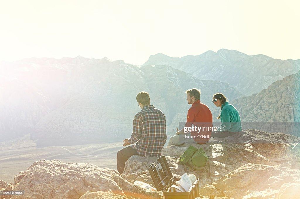 Three friends sitting on mountain top : Stock Photo