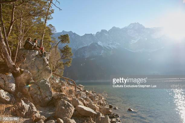 Three friends, sitting on rock beside lake, looking at view, Garmisch-Partenkirchen, Bavaria, Germany