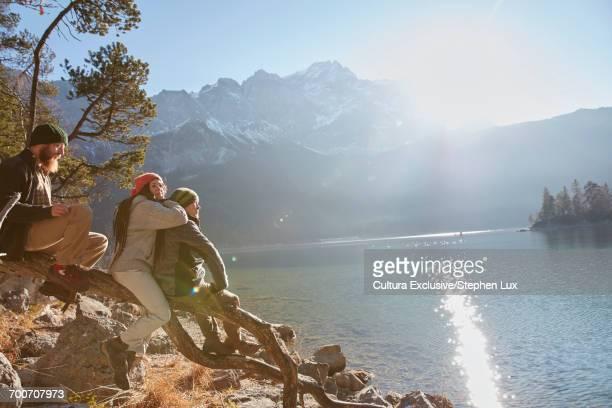 Three friends, sitting on tree beside lake, looking at view, Garmisch-Partenkirchen, Bavaria, Germany