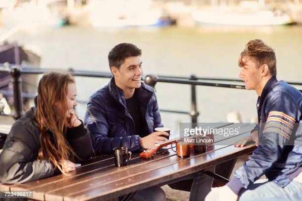 Three friends sitting outdoors, drinking hot drinks, Bristol, UK