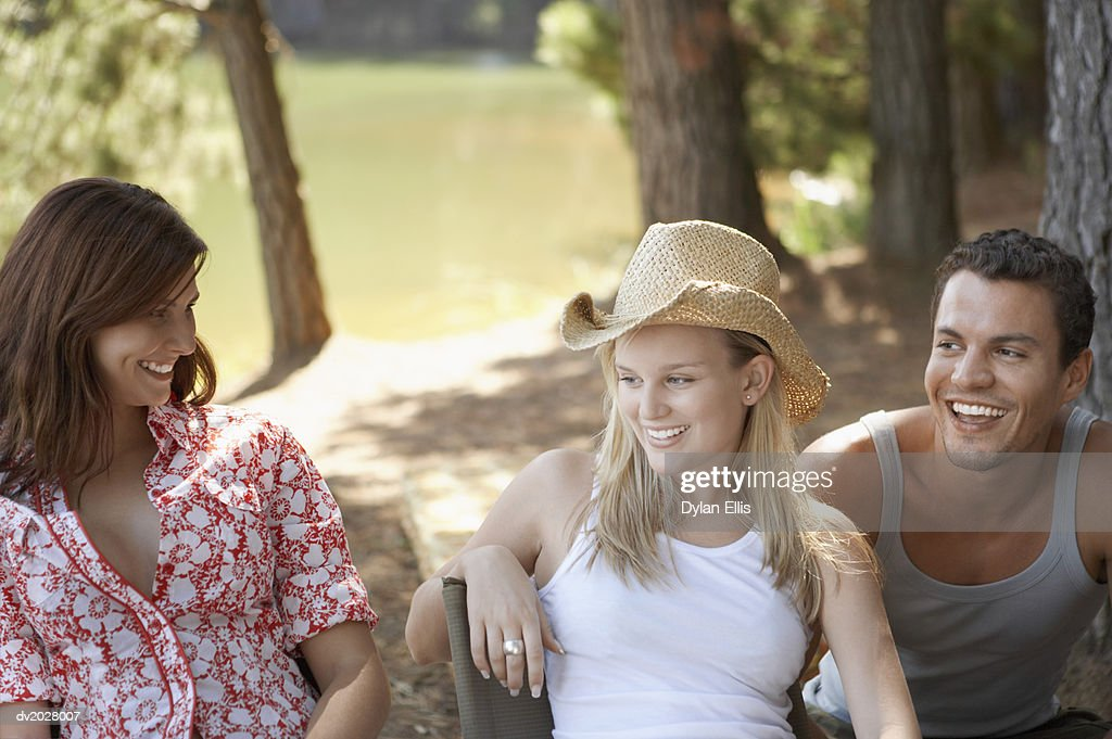 Three Friends Sitting Outdoors in a Forest : Stock Photo
