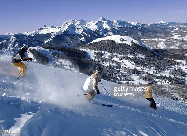 Three friends skiing fresh powder