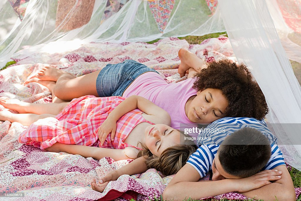 Three friends sleeping in summer netting tent : Stock Photo