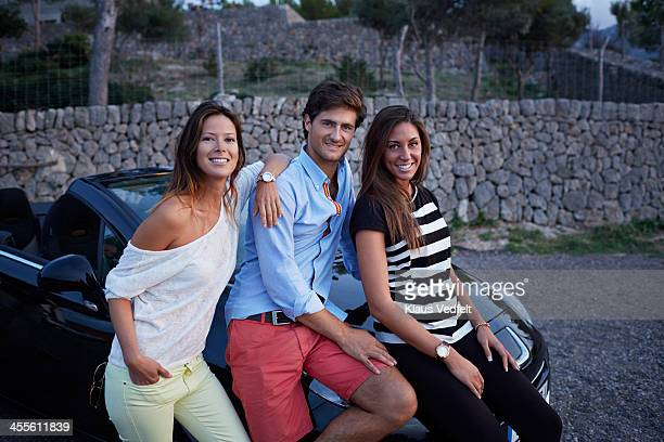 three friends smiling & hanging out by their car - klaus vedfelt mallorca stock pictures, royalty-free photos & images