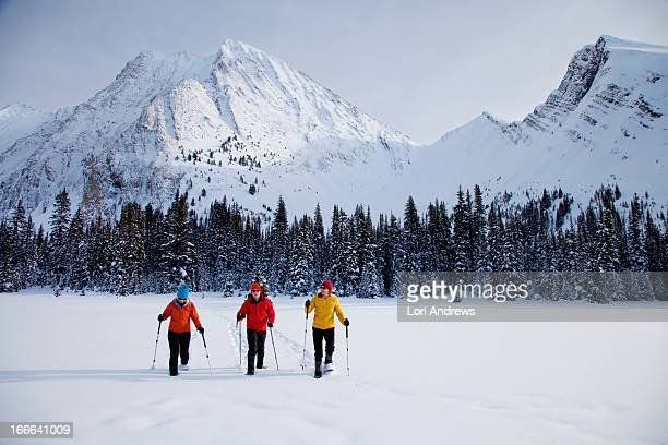 three friends snow shoeing on a snow covered lake - kananaskis country stock pictures, royalty-free photos & images