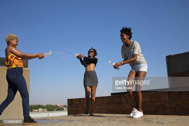 Three friends spraying each other with water bottles