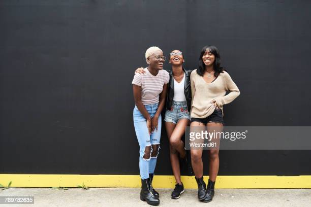 three friends standing against black background having fun - black people laughing stock photos and pictures