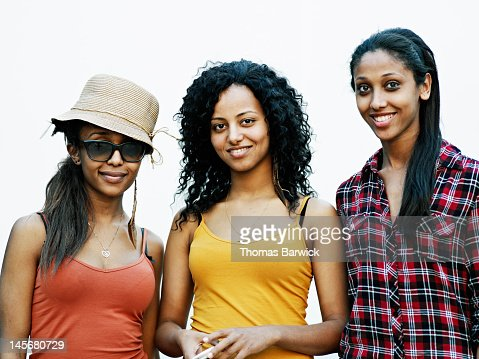 Three friends standing against white background