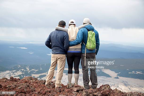 Three friends standing at the summit of South Sister volcano, looking at view, Bend, Oregon, USA