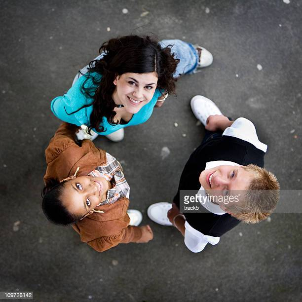three friends standing in a circle looking up and smiling