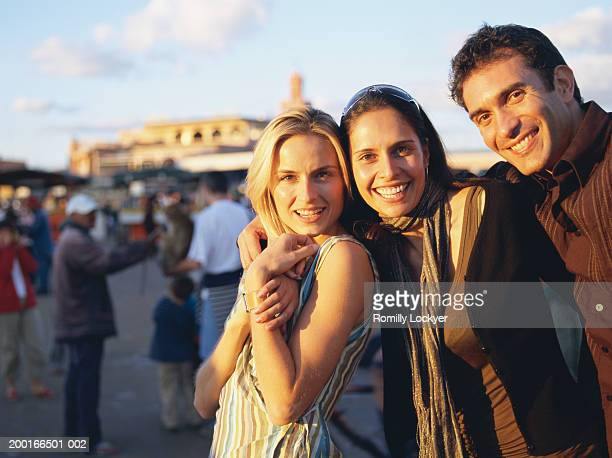 three friends standing together in town square, smiling, portrait - homme maghrebin photos et images de collection