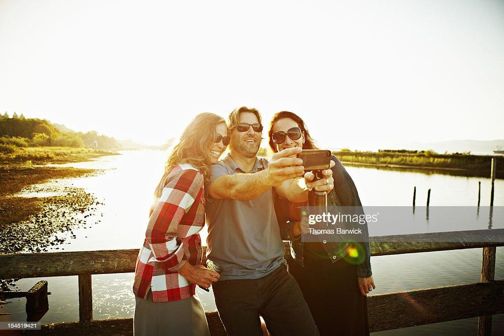 Three friends taking self portrait with smartphone : Foto de stock