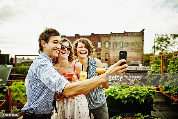 Three friends taking self portrait with smartphone