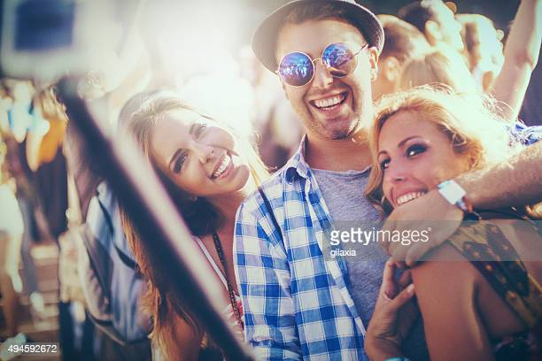 Three friends taking selfies at a party.