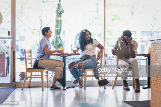 three friends talking and laughing in cafe - bisexuality stock pictures, royalty-free photos & images
