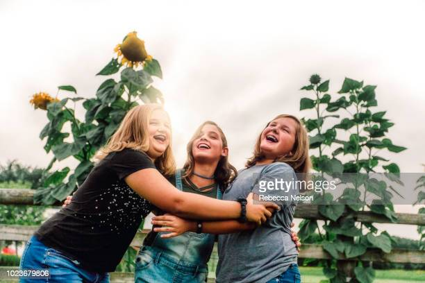 three friends talking and laughing on a summer evening