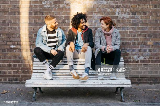 three friends talking on a bench in front of a brick wall - three people fotografías e imágenes de stock