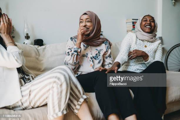 three friends talking together sitting on the sofa at home - mediterranean culture stock pictures, royalty-free photos & images