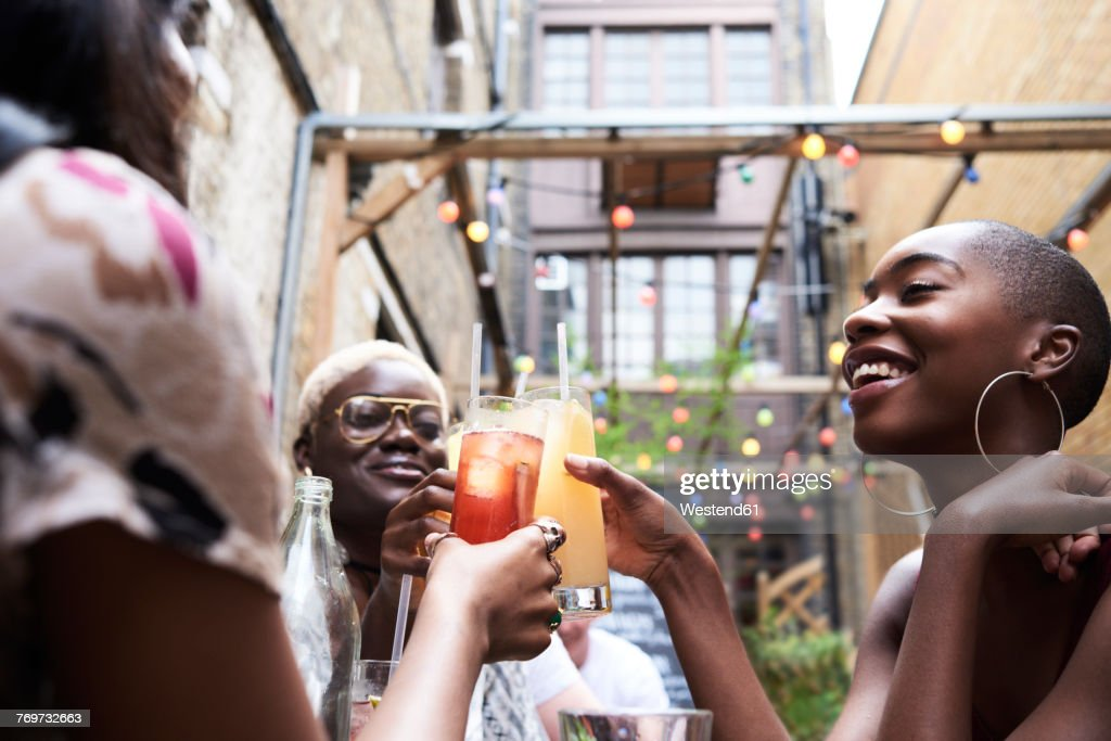 Three friends toasting with cocktails : Stock Photo