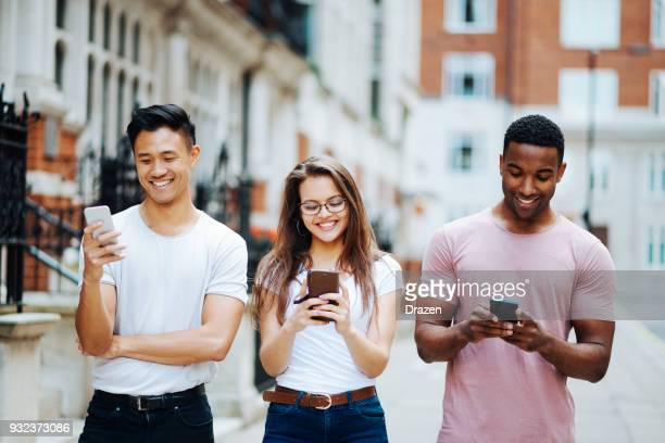 Three friends using their mobile phones