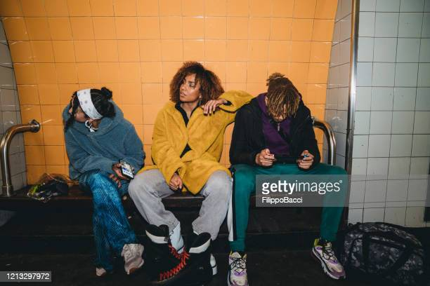 three friends waiting for the train in a subway station - generation z stock pictures, royalty-free photos & images
