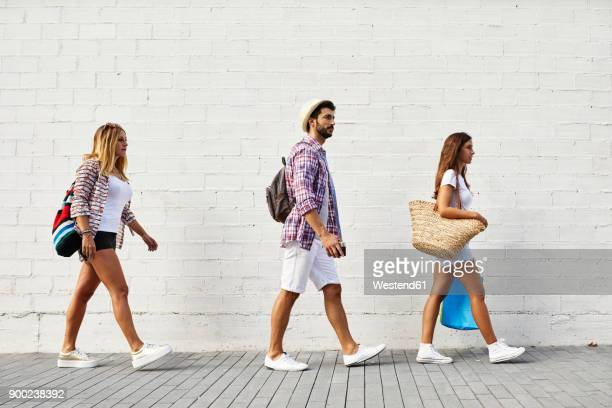 three friends walking along white wall - shorts stock pictures, royalty-free photos & images
