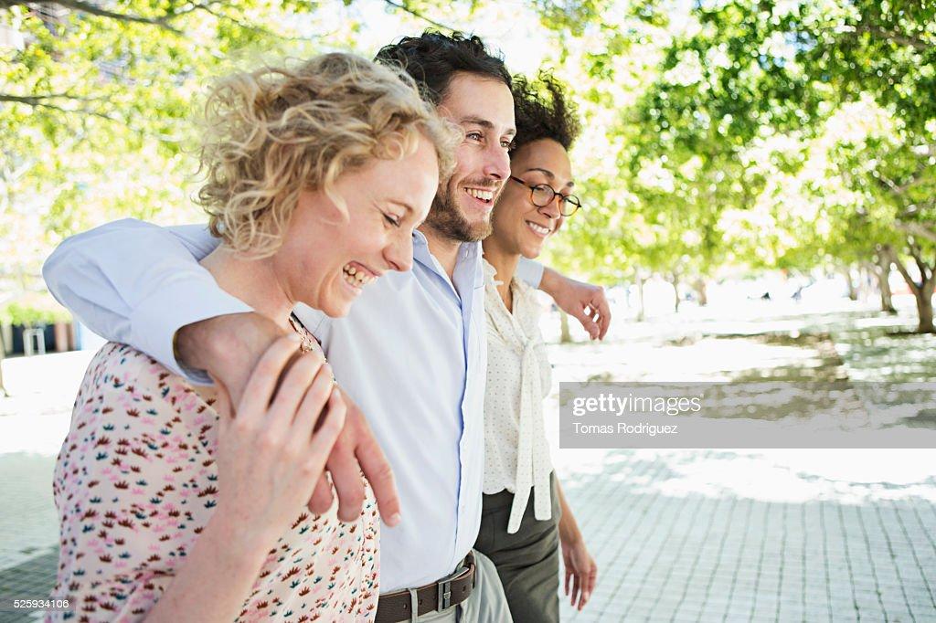 Three friends walking in park : Foto de stock