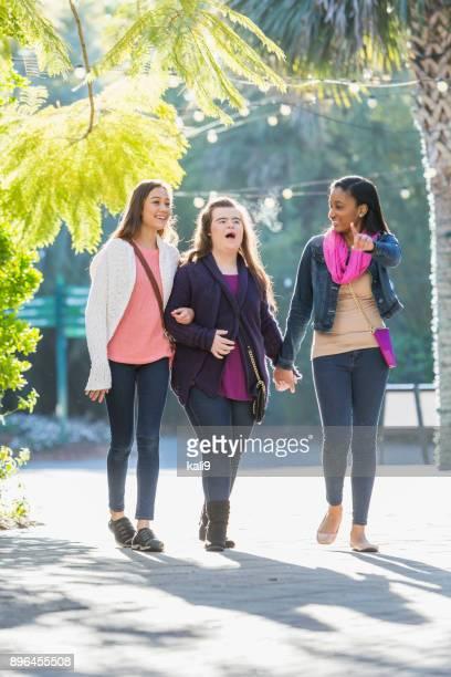 Drei Freunde gehen, Teenager-Mädchen mit Down-Syndrom