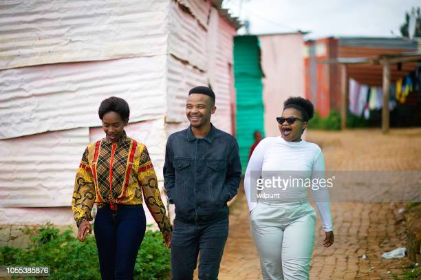 three friends walking together in township smiling - township stock pictures, royalty-free photos & images