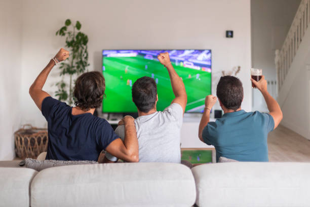 three friends watching a soccer game at home drinking beer picture