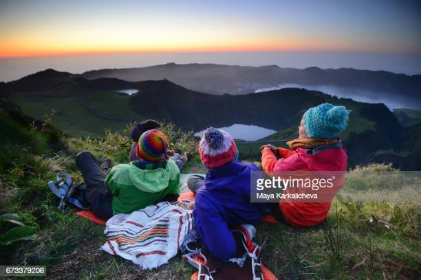 three friends watching the sunset at sete cidades, azores - las azores fotografías e imágenes de stock