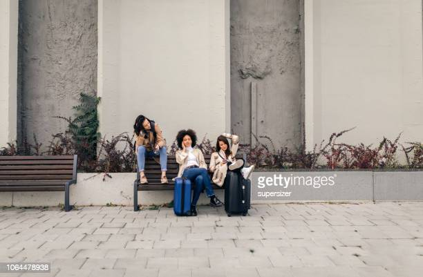 Three friends with suitcases sitting on the bench and resting