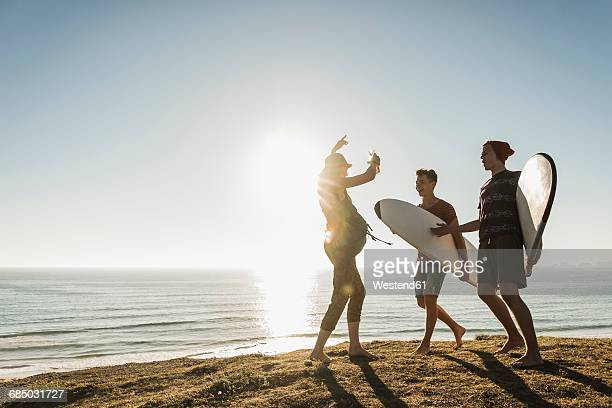 Three friends with surfboards camping at seaside