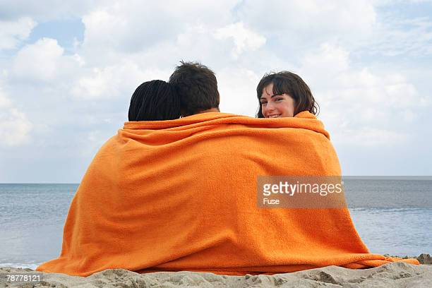 Three Friends Wrapped in Towel on Beach