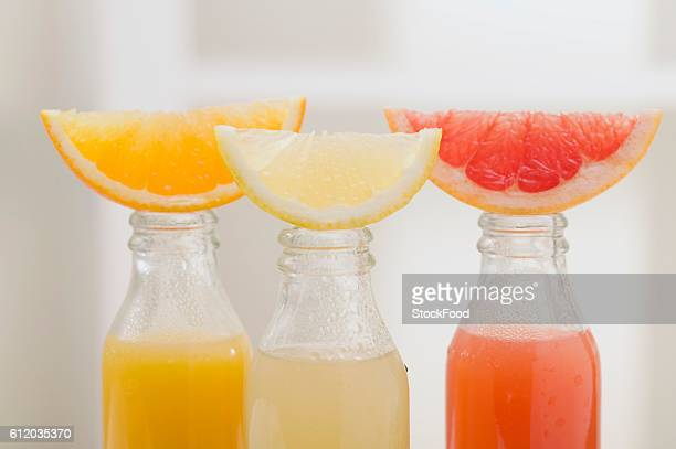Three fruit juices in bottles with wedges of fresh fruit