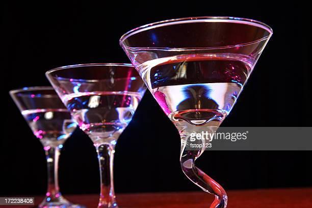 Three full martini glasses in a row. Night. Club.