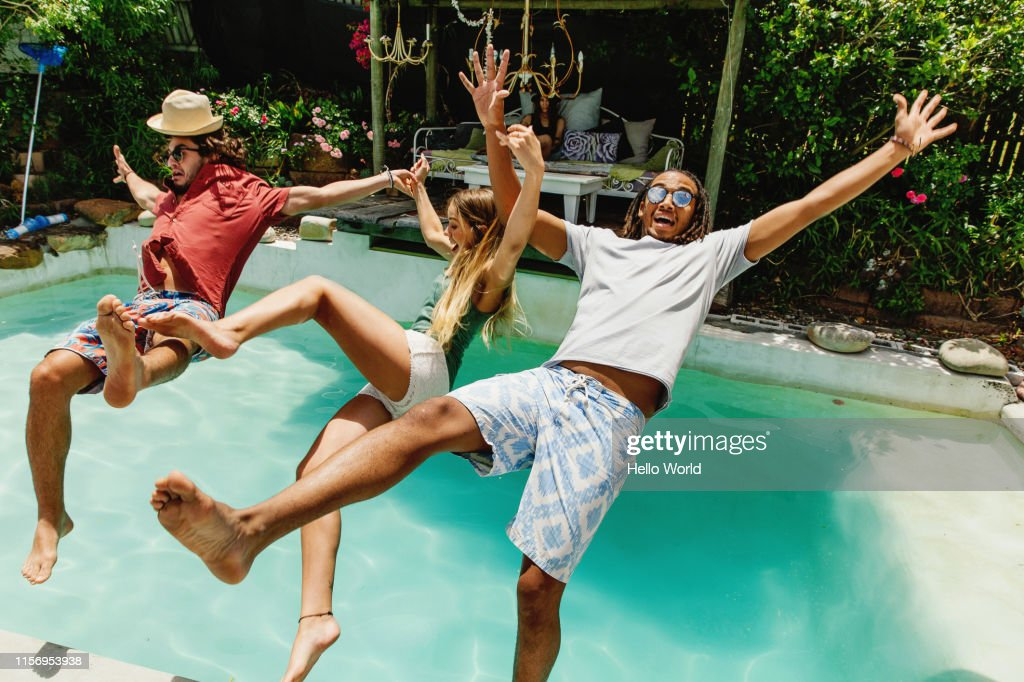 Three fully clothed friends falling backwards into pool : Foto de stock
