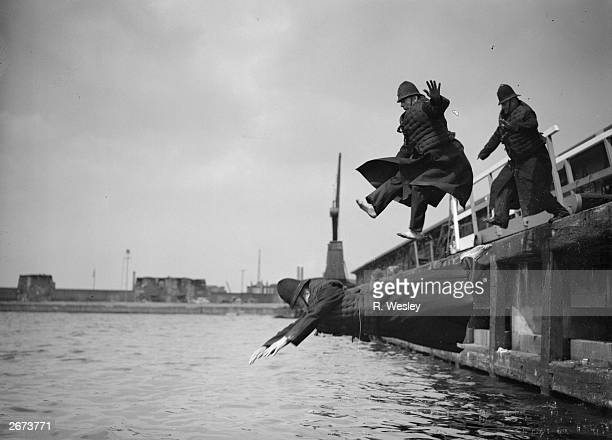 Three fullyclothed members of the Port of London Authority Police jump into the West India Docks during the annual test of their life jackets