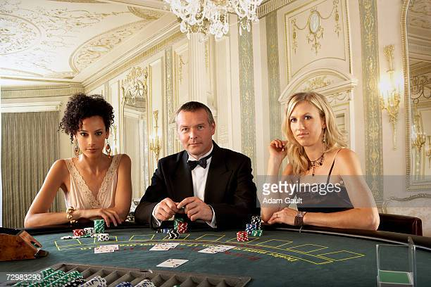 three gamblers at blackjack table in casino, portrait - gambling table stock pictures, royalty-free photos & images