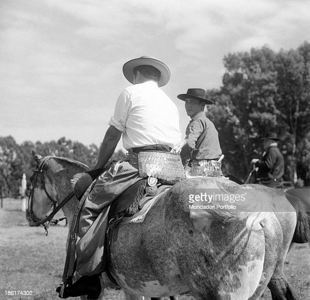 Three gauchos on horseback in the pampa they are the typical South American cattlemen the equivalent of North American cowboys found in the pampas in...