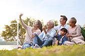 three generation asian family taking selfie outdoors